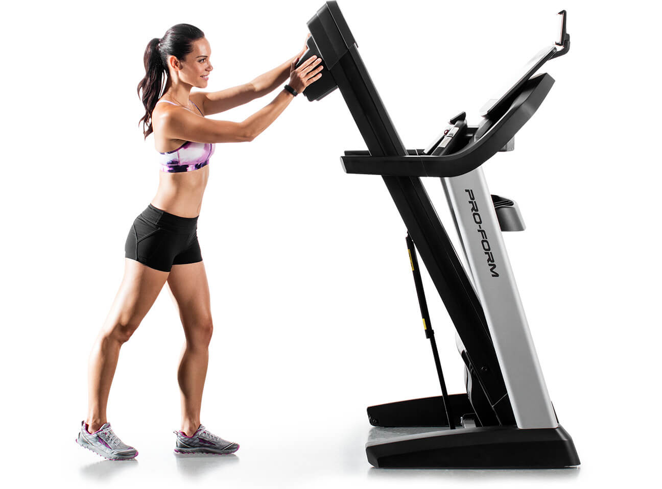 Treadmill in space-saving position with superimposed image of the various stages of the space-saving process